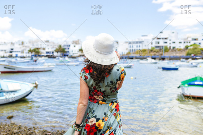 Rear view of woman with white sun hat at harbor in Arrecife- Spain
