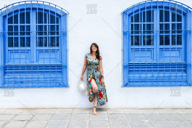 Smiling woman with dress among blue windows