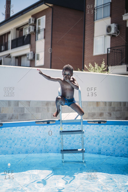 Happy little boy on a ladder of the swimming pool