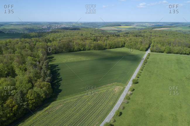 Aerial view of road through agricultural fields and forest- Franconia- Bavaria- Germany