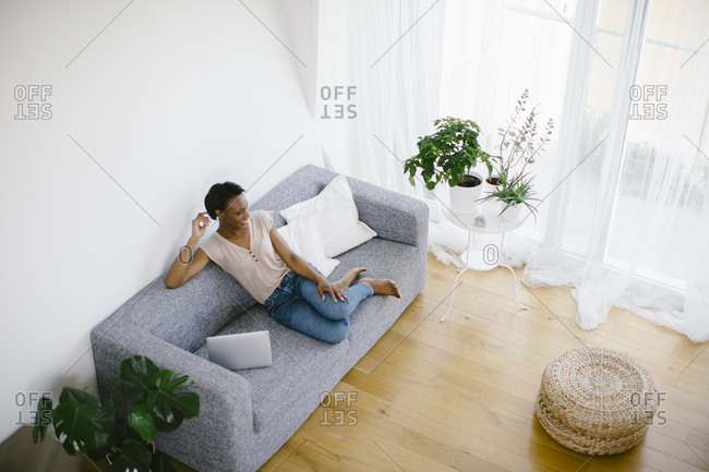 Smiling woman sitting on couch at home with laptop