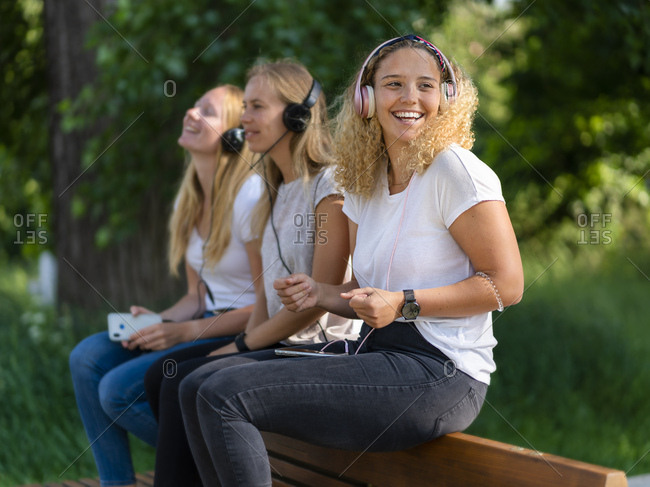 Three young women listening music with headphones and smartphones on a backrest of a bench