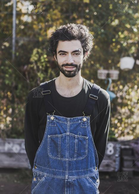 Portrait of smiling man wearing denim dungarees in garden