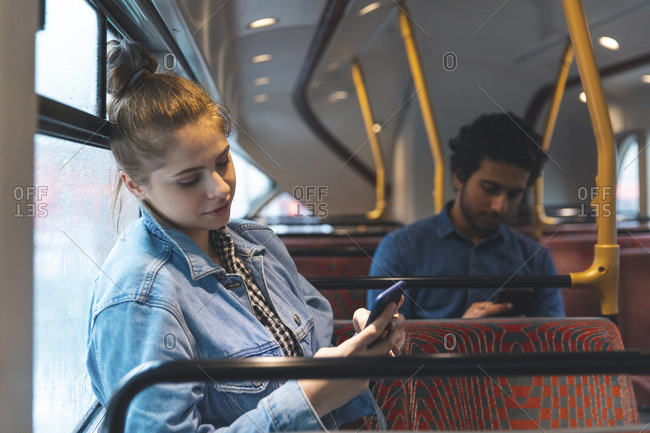 Man and woman using mobile phones in the bus