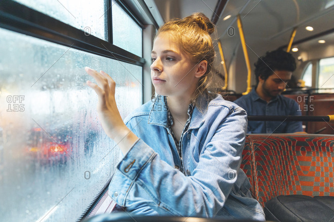 Young woman in bus writing on fogged windowpane with her finger- London- UK