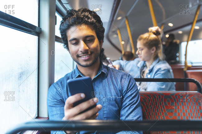 Portrait of young man travelling by bus looking at cell phone- London- UK