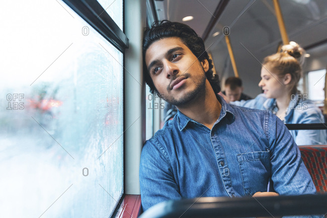 Portrait of daydreaming young man travelling by bus- London- UK