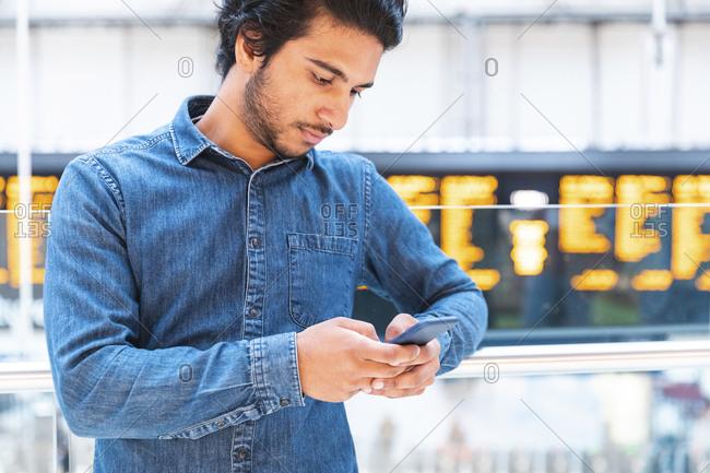 Young man wearing denim shirt using smartphone at train station- London- UK