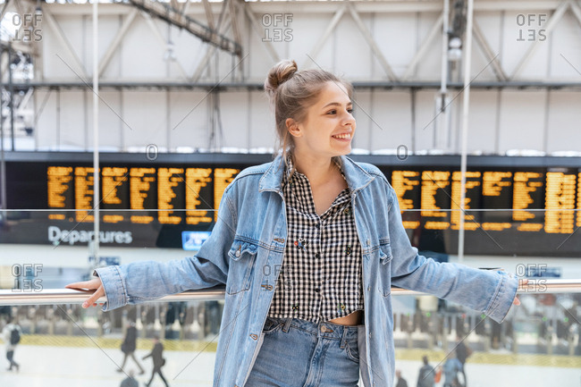 Portrait of happy young woman at train station- London- UK