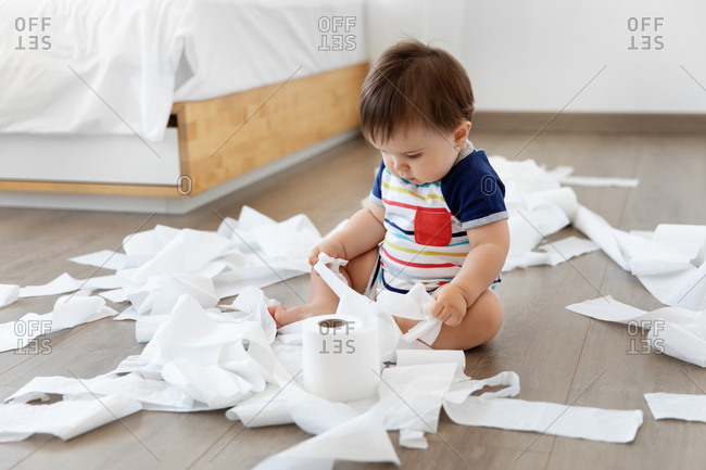 Baby sitting on floor making mess with toilet paper