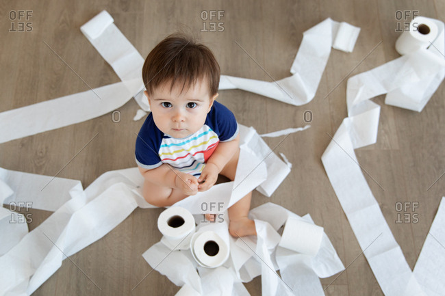 Overhead view of baby making mess with toilet paper