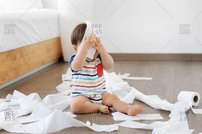 Cute baby hiding face with toilet paper
