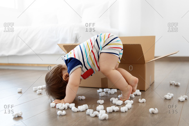 Funny baby crawling next to cardboard box