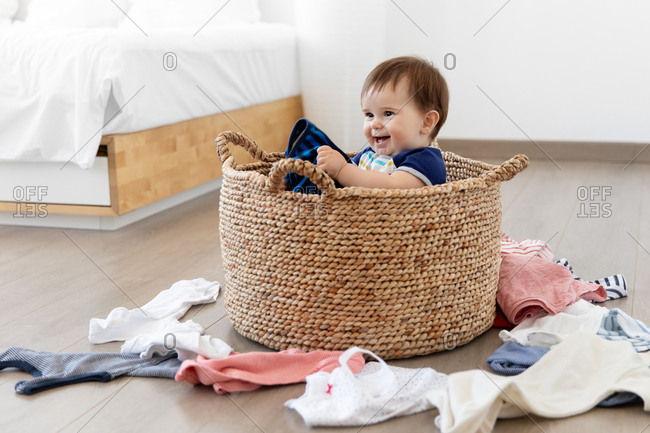 Smiling baby sitting in laundry basket