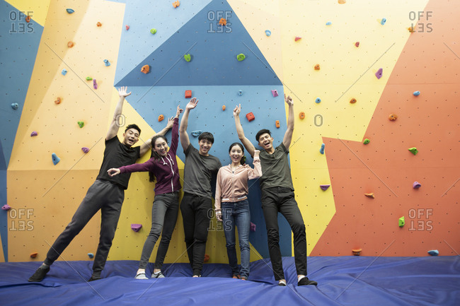 Happy young Chinese friends standing against climbing wall at gym