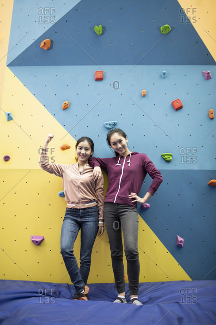 Happy young Chinese women standing against climbing wall at gym