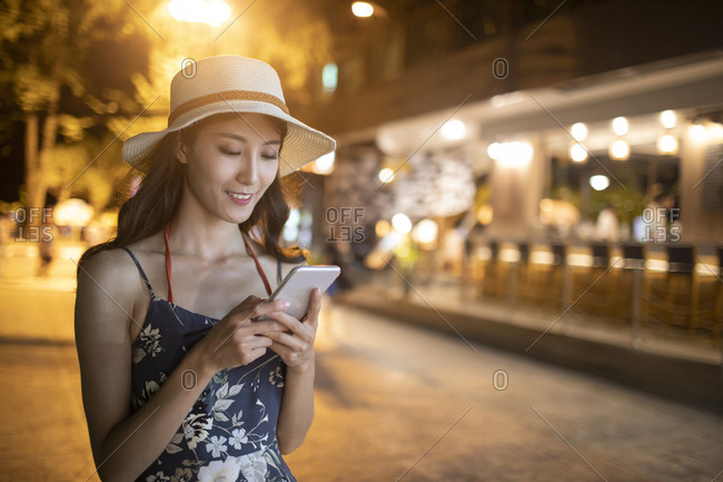 Happy young Chinese woman using smartphone