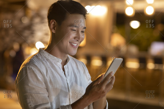 Happy young Chinese man using smartphone