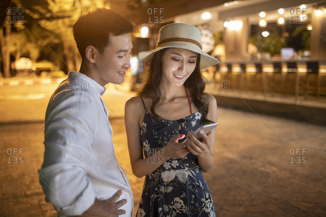 Happy young Chinese couple using smartphone