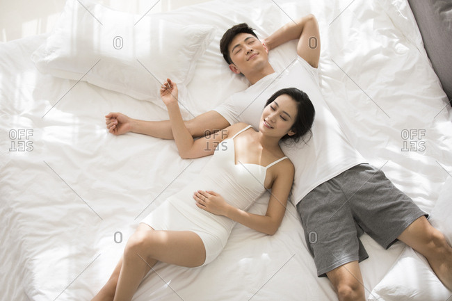 Happy young Chinese couple sleeping on bed