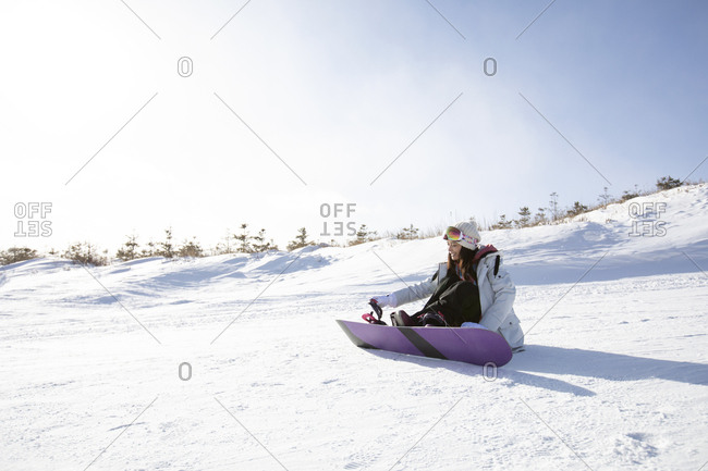 Happy young Chinese woman skiing in ski resort