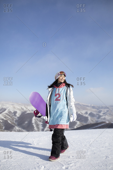 Happy young Chinese woman walking in ski resort
