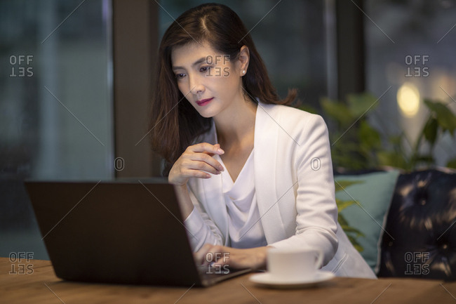 Chinese businesswoman using laptop in cafe