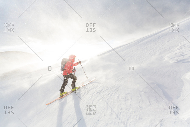 Man backcountry skiing up a snowy mountain