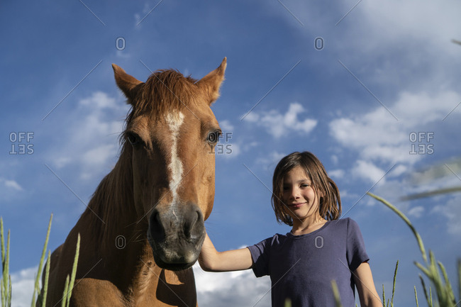 Low angle portrait of girl standing by horse against blue sky