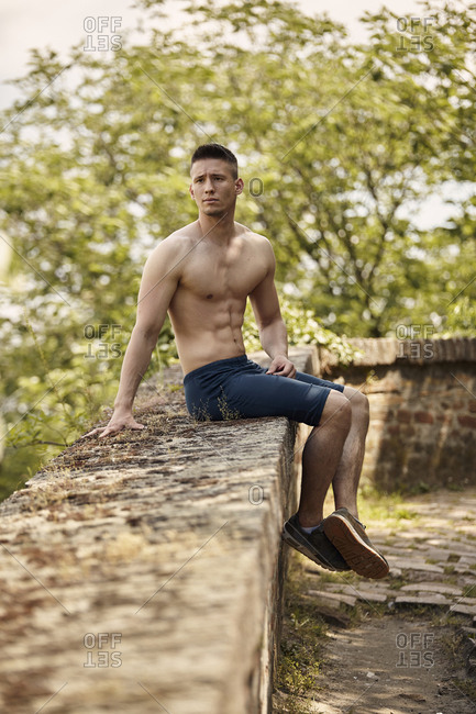 Thoughtful shirtless man looking away while sitting on retaining wall