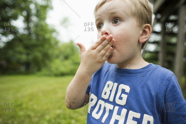 Surprised boy looking away while covering mouth in backyard