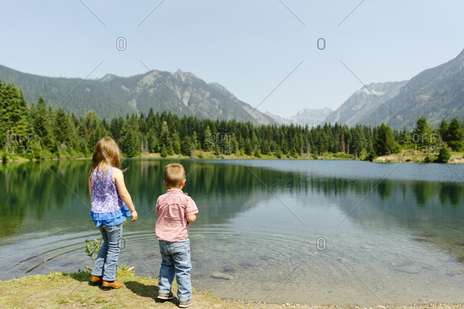 Rear view of two young children standing in front of a mountain lake