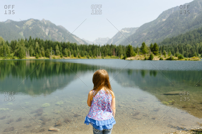 Rear view of a young girl standing in front of a mountain lake