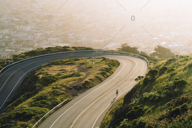 Aerial view of winding road on mountain against cityscape during sunset