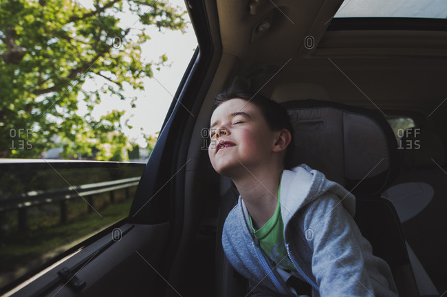 Cute boy with eyes closed traveling in car
