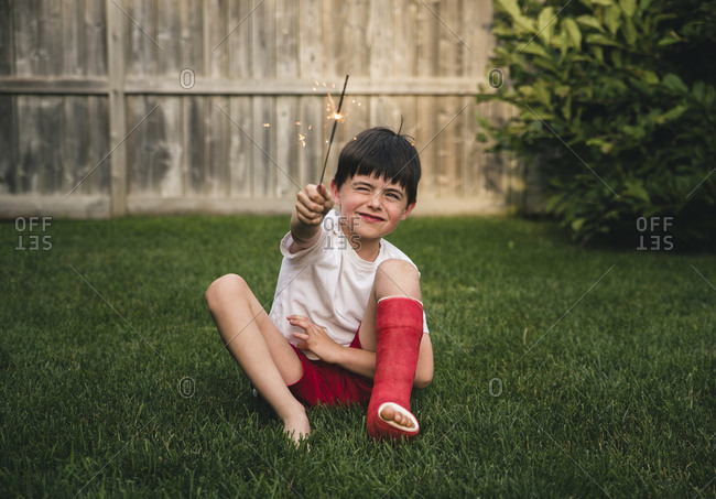 Happy boy with broken leg holding sparkler while sitting on grassy field in yard