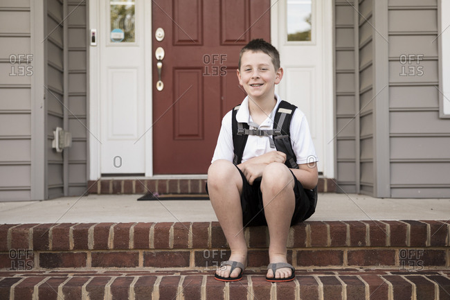Tween Boy With Braces Sits on Brick Front Step, First Day of School