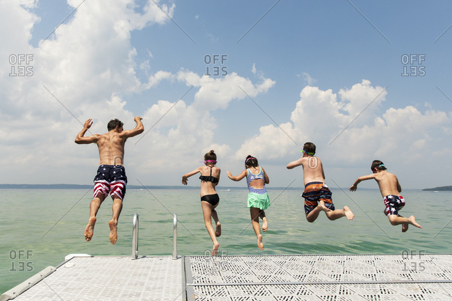 Group of Cousins Jumping off Dock Into Lake Michigan on a Sunny Day