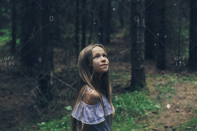 Girl looking up while standing in forest
