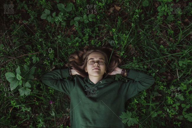 High angle view of teenage girl sleeping on field in forest