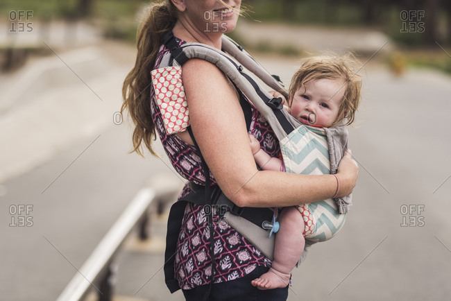 Midsection of smiling mother carrying cute daughter while standing on road in park