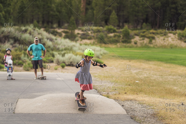 Family looking at girl skateboarding on road against trees in park