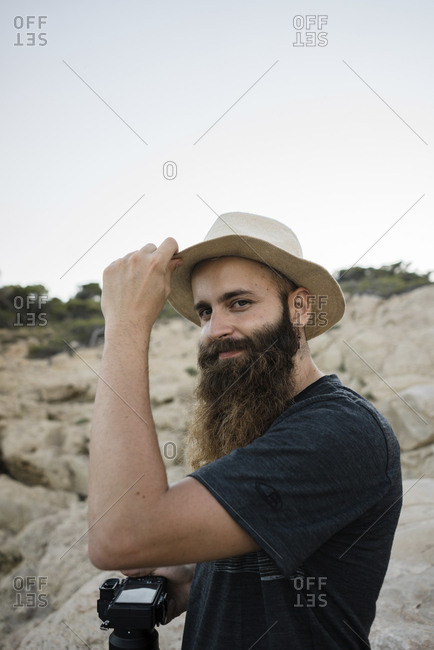 Side view portrait of bearded tourist with camera wearing hat while standing on rocks