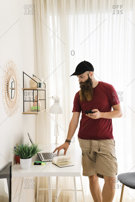 Bearded editor using laptop computer while standing at home