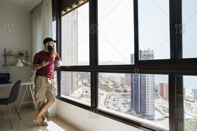 Full length of thoughtful bearded man looking through window while holding mobile phone and coffee cup at home