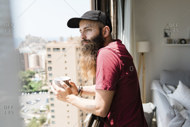 Side view of thoughtful bearded man looking through window while holding coffee cup at home