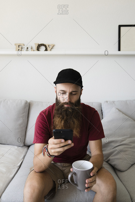 Bearded man using mobile phone while holding empty coffee cup on sofa at home