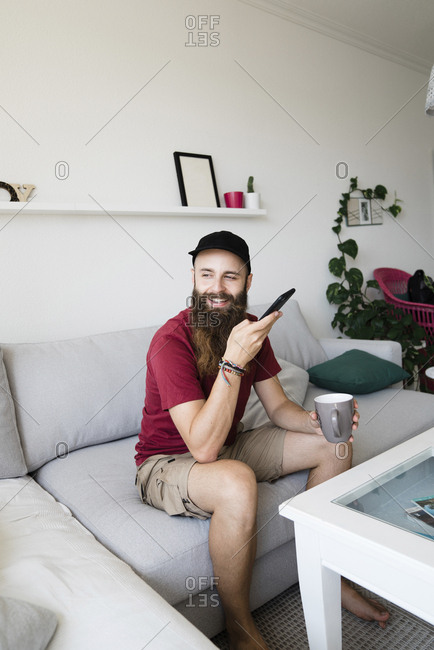 Smiling bearded man holding mobile phone and coffee cup while sitting on sofa at home
