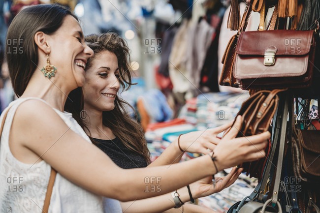 Happy female friends buying purse at market