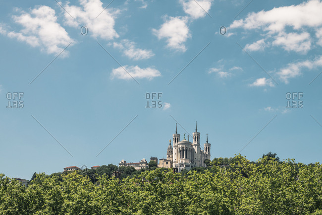 Low angle view of Basilica Notre Dame de Fourviere against blue sky in city during sunny day